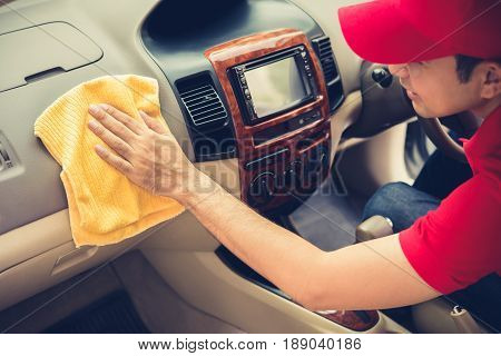 A man cleaning car interior - car detailing and valeting concept vintage tone effect