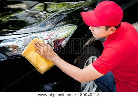 Auto service staff in red uniform cleaning car with microfiber cloth - car detailing and valeting concepts
