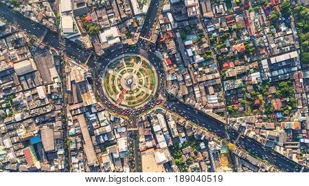 Road roundabout with car lots Wongwian Yai in BangkokThailand. street large beautiful downtown at evening light. Aerial view Top view cityscape Rush hour traffic jam