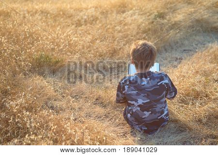 Boy reading book in yellow grass high in the hills, trail winding ahead of him, rear view