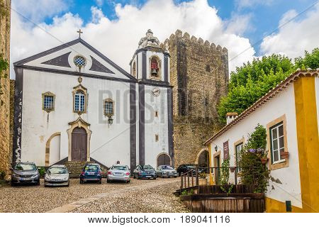 OBIDOS,PORTUGAL - MAY 11,2017 - View at the Santiago church in streets of Obidos. The area of the town of Obidos is located on a hilltop encircled by a fortified wall.