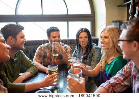 people, leisure, friendship and communication concept - happy friends drinking beer and talking at bar or pub