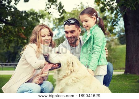 family, pet, domestic animal and people concept - happy family with labrador retriever dog on walk in park