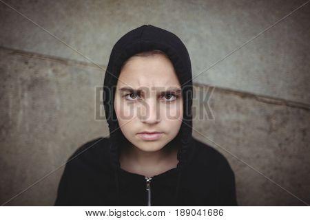 Portrait of anxious teenage girl in black hooded jacket standing at school