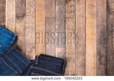 Jeans on wood background top view with copy space