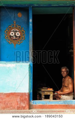 PURI INDIA - 18 DECEMBER 2009: Soothsayer sitting in the door of his house waiting for pilgrims in order to tell them fortune