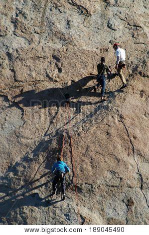 Rock Climbers scale rocks at Lake Perris CA