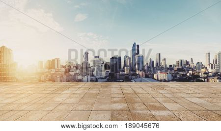 Panoramic city view in sunrise with empty wooden floor