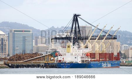Oakland CA - May 30 2017: Bulk carrier MOUNT HIKURANGI loading at Schnitzer Steel at the Port of Oakland. Schnitzer Steel recycles scrap metal into finished steel products.