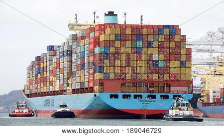 Oakland CA - May 30 2017: Multiple tugboats assist cargo ship GERDA MAERSK to maneuver into the Port of Oakland the fifth busiest port in the United States.