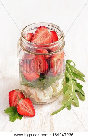 Healthy Salad Dish With Fresh Strawberry, Arugula And Soft Cheese In Glass Jar