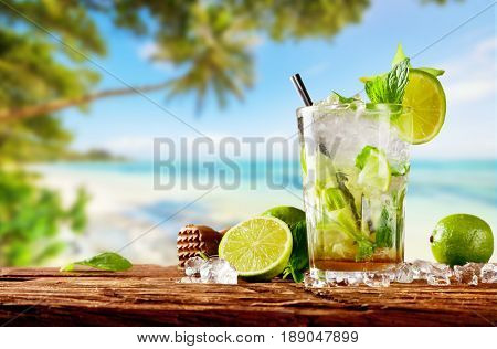 Fresh mojito drink placed on wooden planks, blur tropical beach on background. Summer drinks and beach vacation background