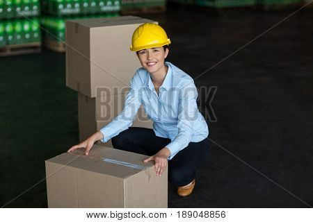 Portrait of female factory worker picking up cardboard boxes in factory
