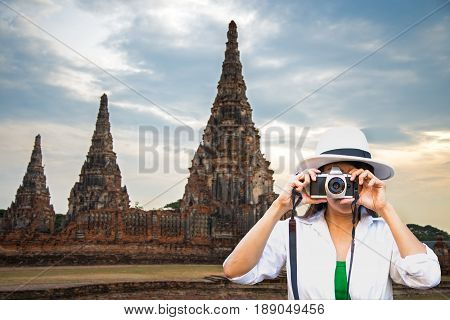 Traveler women covering her face with the camera in the Ayutaya Thailand
