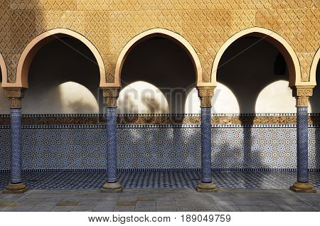 Berlin, Germany - April 13, 2017: Arcade with oriental patterns and contrasting shadows in the East garden. Gardens of the world in Berlin.