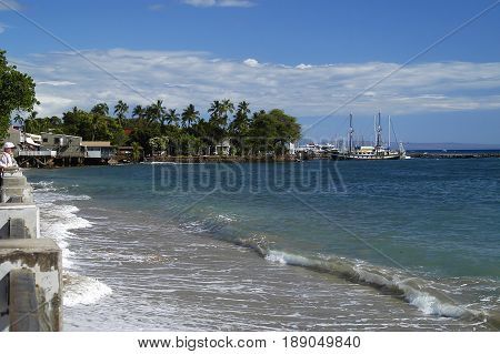 Gentle waves break on white sand beach in Lahaina Maui HI