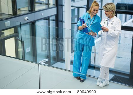 Female doctor and nurse discussing over a medical report in hospital