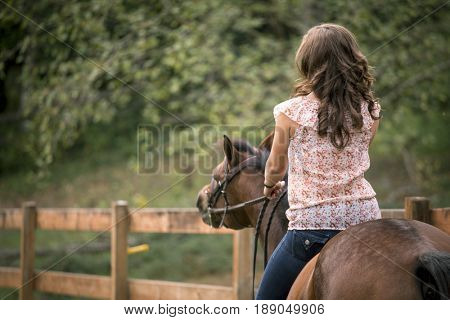 Caucasian woman riding horse in pen