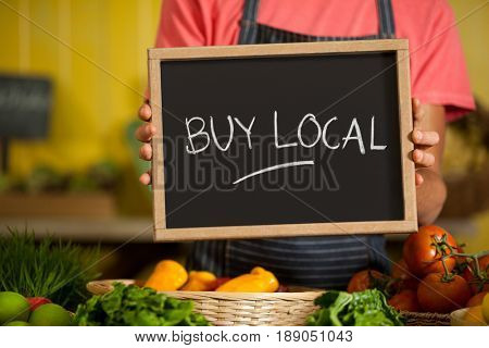 Mid section of male staff holding slate board in organic section of supermarket