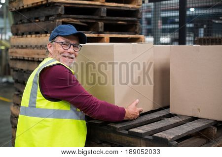 Factory worker loading cardboard boxes on trolley in drinks production factory