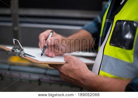 Mid section of male factory worker maintaining record on clipboard in drinks production factory