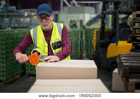 Factory worker sealing cardboard boxes in drinks production factory