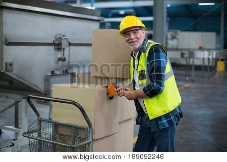 Portrait of factory worker loading cardboard boxes in drinks production factory