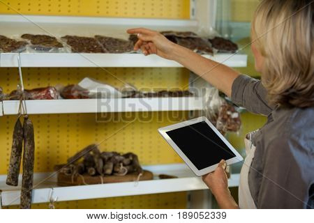 Female staff maintain records of meat on digital tablet at counter of supermarket