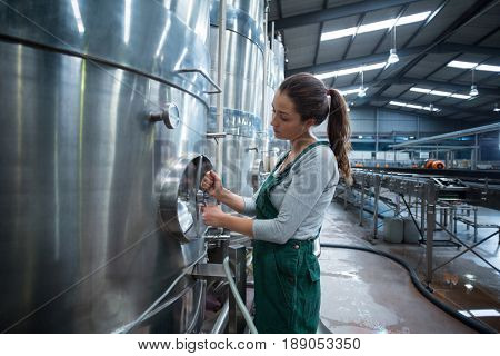 Female factory worker turning control wheel of storage tank at drinks production factory