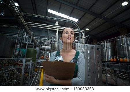 Female factory worker maintaining record on clipboard in drinks production factory poster