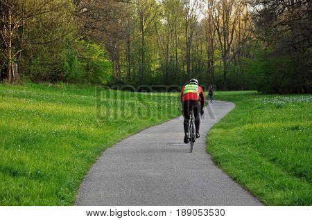 Waiblingen, Baden-Wurttemberg, Germany - April 21, 2017: A cyclist riding along the bicycle path and a woman running towards him.