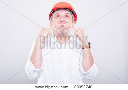 Portrait Of Contractor Wearing Hardhat Making Silly Gesture