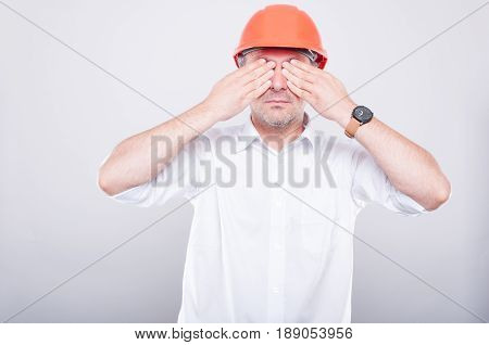Portrait Of Contractor Wearing Hardhat Covering His Eyes