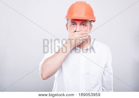 Portrait Of Contractor Wearing Hardhat Covering His Mouth