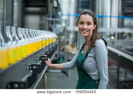 Portrait of female factory worker standing near production line at drinks production factory