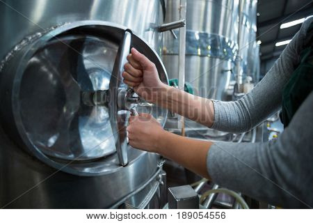 Mid section of female factory worker turning control wheel of storage tank in drinks production factory