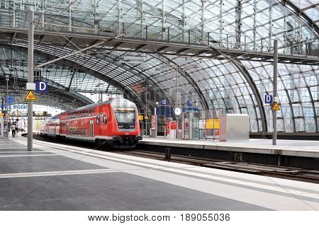 Berlin, Germany - April 16, 2017: Platform of the Berlin railway station under glass ceiling and the red train standing on the rails.