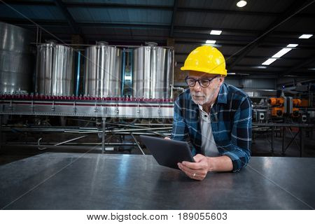 Factory worker using digital tablet at drinks production factory