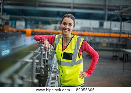 Portrait of smiling female factory worker standing next to production line at drinks production factory