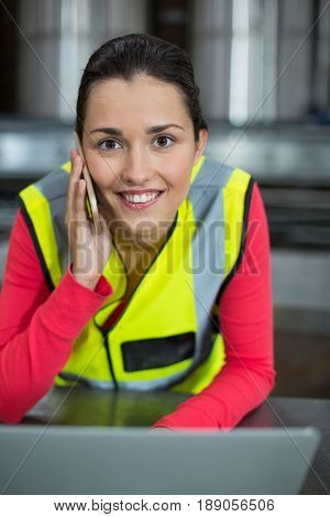 Portrait of female factory worker using laptop while talking on mobile phone at drinks production factory