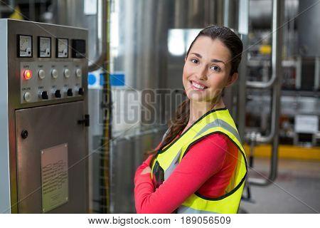 Portrait of female factory worker standing near machine in bottle factory