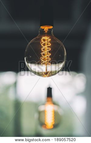 Vintage Edison Light Bulb Hanging With Other Light Bulbs Indoors With Copy Space