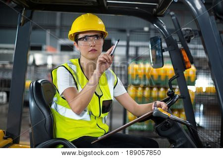 Attentive female factory worker sitting on forklift and writing in clipboard at factory
