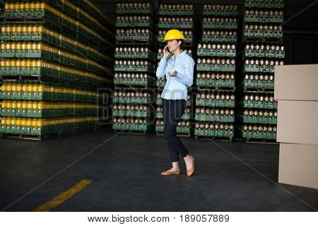 Female factory worker talking on mobile phone in factory