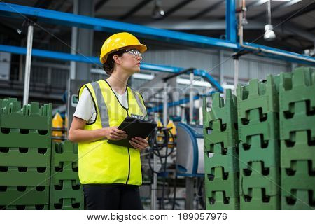 Female factory worker maintaining record on digital tablet in factory