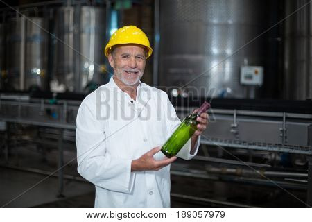 Portrait of factory worker examining a bottle in factory