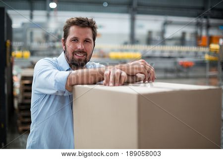 Portrait of smiling factory worker standing in factory