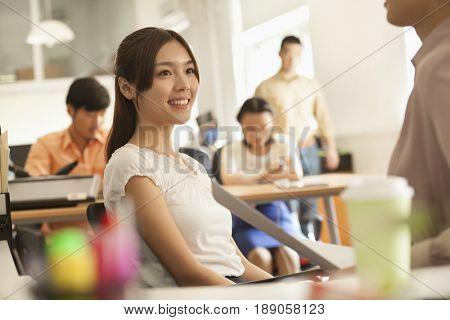 Chinese businesswomen talking at desk