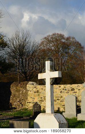 White Christian cross in cemetery at Adare Ireland.