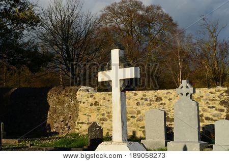 White stone cross in Adare cemetery beside the monastery.